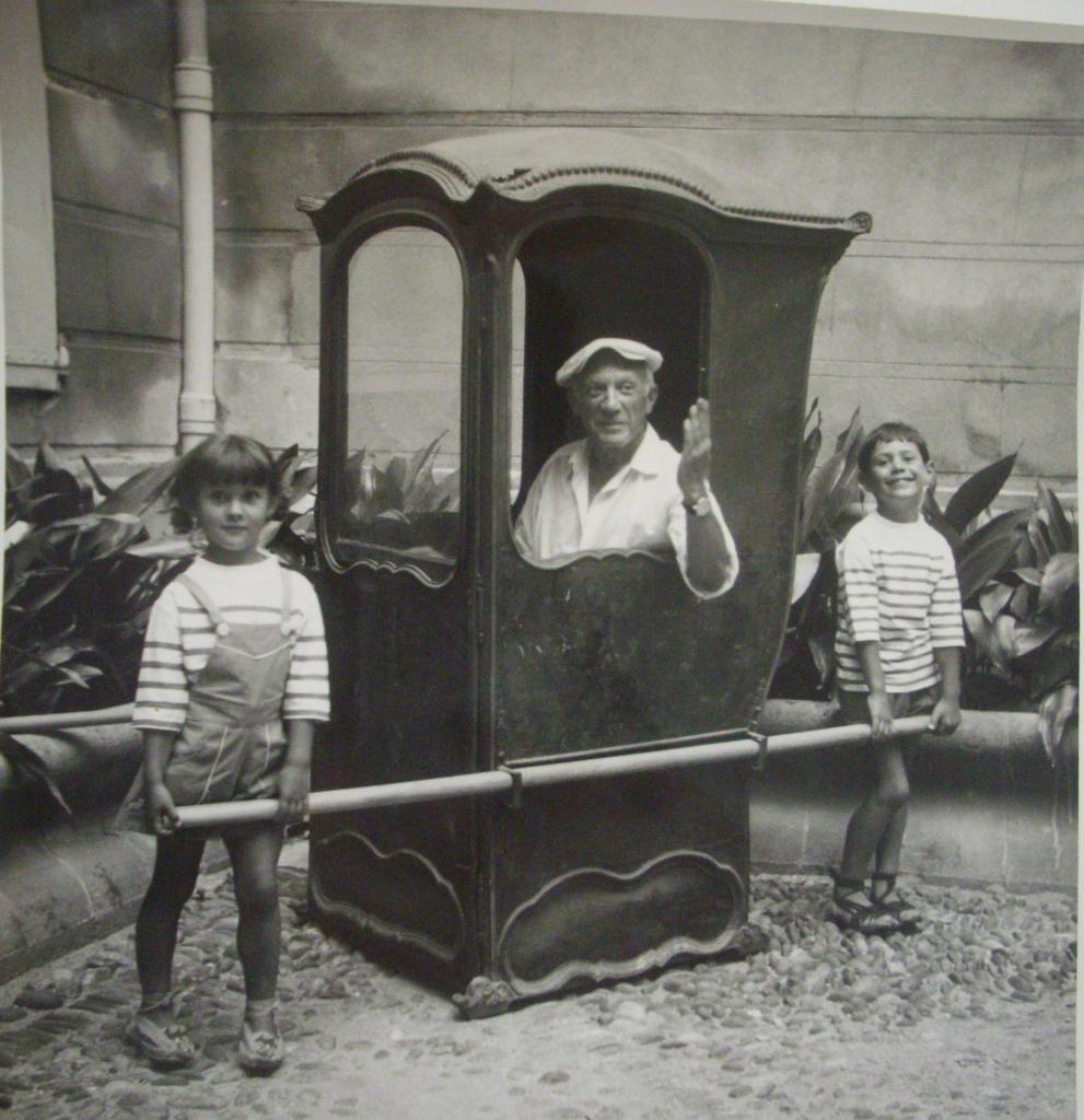 Picasso dans une chaise a porteurs entoure de Claude et Paloma, cour de l'hotel de Lazerme, 1954 - Exposition Picasso a Perpignan au Musee d'Art Hyacinthe Rigaud