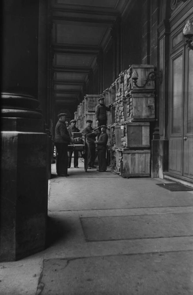 Dépôt des caisses d'archives sous la colonnade de la cour de Soubise en vue de leur réintégration. Les agents vident les caisses de transport contenant des registres. 1940, Exposition Chaos, Archives Nationales