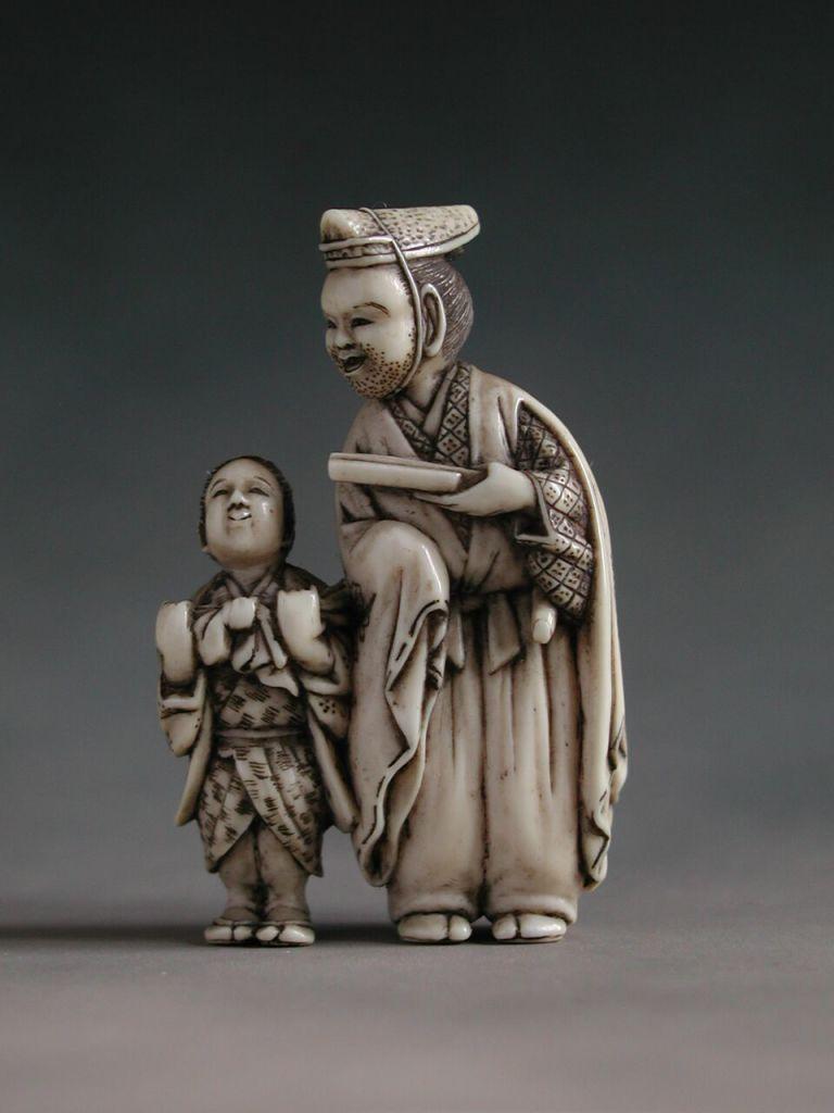 Netsuke. Homme noble et enfant portant un sac par Minkoku